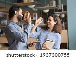 Small photo of Two happy friendly diverse professionals, teacher and student giving high five standing in office celebrating success, good cooperation result, partnership teamwork and team motivation in office work.