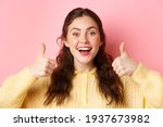 Small photo of Close up of cute happy woman showing her support, making thumbs up in approval, say yes, nod and agree, standing against pink background