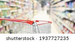 Small photo of empty red shopping cart in supermarket aisle