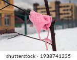 A Lost Pink Wool Baby Hat Hangs ...