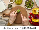 Small photo of Vegetarian food. Chopping cucumber, cutting vegetables for greek salad horiatiki. Woman hands with knife on wooden cutting board slicing chop of vegetables. Homemade vegan food, top view