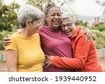 Small photo of Happy multiracial senior women having fun together outdoor - Elderly generation people hugging each other at park