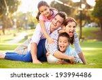 Family Lying On Grass In Park...