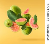 Small photo of Fresh ripe whole and halved guava with leaves falling in the air isolated on yellow illuminating background. Zero gravity or levitation conception. High quality resolution image