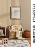 Small photo of Stylish scandinavian kid room interior with toys, teddy bear, plush animal toys, rattan sofa, furniture, decoration and child accessories. Brown wooden mock up poster frames on the wall. Template
