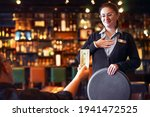Small photo of Waitress takes the tip. The waiter female receives a tip from the client at the hotel bar. The concept of service