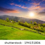 summer landscape. fence near the meadow in village hillside. forest in fog on the mountain at sunset - stock photo