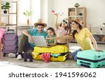 Small photo of Happy excited family and daughter children buying payment for flight ticket booking hotel online using laptop with travel suitcase around at home living room. Holiday vacation traveling abroad concept