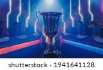 Two Esport Teams of Pro Gamers Play to Compete in Video Game on a Championship. Stylish Neon Cyber Games Online Streaming Tournament Arena with Trophy in the Center.