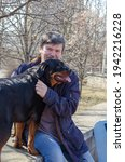 Small photo of Emotional portrait of a grizzled man who misses his pet. The long-awaited meeting of the dog and the owner after a long separation. Dog breed Rottweiler. Outdoors.