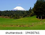 New Zealand farm scene including pasture in foreground and snow capped mountain in the distance. - stock photo