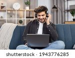 Small photo of Online lessons, e-learning concept. Young likable Indian man sitting on couch in living room at home, enjoying studying using laptop and headset, looking at screen and listening audio lessons.