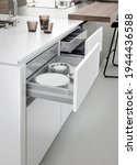 Small photo of Modern kitchen, Open drawers, Set of cutlery trays in kitchen drawer. Stainless steel drawer box side.