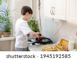 Small photo of teen boy bakes (fries) pancakes in the kitchen. Cooking at home. Teenager boy is learning to cook. Kid boy 12 years old makes crepes by himself on frying pan. Independent child. Novice young chef
