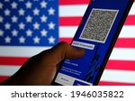 Small photo of New York COVID-19 vaccination passport. Excelsior Pass app demo seen on the smartphone screen with blurred American flag on the background. Stafford, United Kingdom, March 30, 2021.