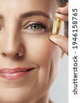 Small photo of Beautiful middle aged woman holding capsule with a fish or krill oil source of Omega-3 fatty acids