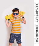 Small photo of Cute little guy in big trendy sunglasses and yellow longboard. Kid boy posing with his skateboard against white wall with copyspace.