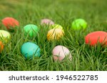 Easter hunt concept. Colourful eggs hidden in green grass.