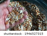 Small photo of A hand holding crushed eggshells. The shells have been baked, then crushed. Crushed eggshells have a variety of uses. Concepts of nutrition, farming, gardening