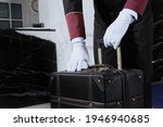A Uniformed Doorman Holds A...