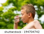 young caucasian boy drinking... | Shutterstock . vector #194704742