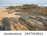 Small photo of cliffs coastal landscape with a wide sandy beach with high boisterous waves in the bay