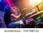 Drummer (blurred motion) playing on drum set on stage. Focus on the drum and microphone. - stock photo