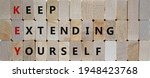 Small photo of KEY, keep extending yourself symbol. Wooden blocks with words 'KEY, keep extending yourself'. Beautiful wooden background, copy space. Business and KEY, keep extending yourself concept.