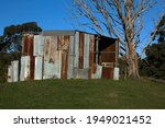 Old rusting corrugated iron hay shed on a hillside in Ferndale, near Warragul, Gippsland, rural Victoria on a warm sunny afternoon.