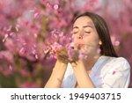 Beautiful Woman Blowing Flower...