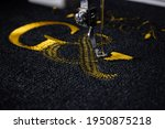 Small photo of Machine embroidery on black velvet fabric with yellow thread. Embroidered initial G. Close up.