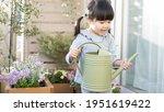Children Watering Flowers On...