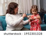 Grandmother Give To Her Cute...