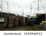 Bunch of crab traps, cages, traps, nets, and other equipment for seafood hunting and harvesting on a grey gloomy day in Milford marina, Connecticut.