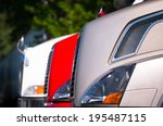 Hoods modern trucks of different colors with chrome grilles and prominent headlights standing in a row against a blurred background of green trees - stock photo