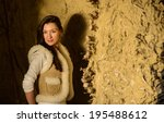 Small photo of Young woman looking at the camera against artless wall