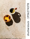 Small photo of Coffee and Pastel de Nata Fresh baked Portuguese egg custard Tart on beige stone background