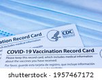 Small photo of Closeup. Covid-19 vaccination record cards issued by CDC, United States Centers for Disease Control and Prevention, on a blue disposable face mask - San Jose, California, USA - 2021
