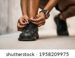 Small photo of Athletic woman tying her shoelaces.
