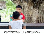 Brother and yong brother sitting and playing under big Giant Monky Pod Tree