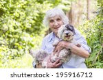 Stock photo senior smiling woman hugging her dog in the mountain 195916712