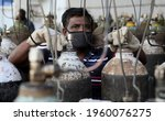 Small photo of New Delhi, India, April 21, 2021: Worker refilling medical oxygen cylinder for Covid-19 infections patients at a gas supplier filling station during the second wave of coronavirus Covid-19 pandemic.