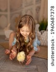 Cute happy small blond girl playing with a yellow chick on easter holiday