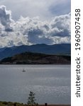 Small photo of Hillside and mountains with some fall foliage behind sailboat on Lake Dillon, Colorado, on partly cloudy late summer day with some sun shining through the clouds