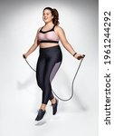 Small photo of Sporty girl with skipping rope in motion