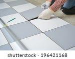 Tiler install ceramic tiles on  floor - stock photo