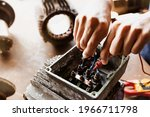 Small photo of 380 volt electric motor inspection work : Top view electrician mechanic's hand uses a voltmeter tool to check the operation and the tightening of the circuit for safety.