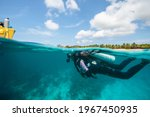 Small photo of A scuba diver swimming back to the boat on a tropical island of Utila, Bay Islands, Honduras, Central America, over-under photo, split shot, splits, Carribean sea diver, PADI, SSI certified diver