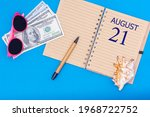 21st day of august. Travel concept flat lay - notepad with the date of 21 august pen, glasses, dollars and seashell on blue background. Summer month, day of the year concept.
