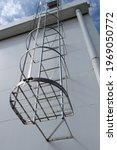 Small photo of Aluminum cat ladder with cage. Outdoor fire escape, It is installed on the side of the building in the bottom view. Fire escape stairs outside the building.